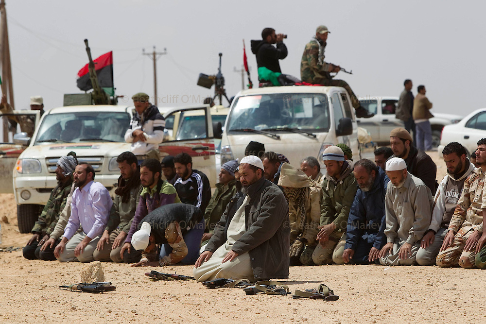 Mcc0030300 . Daily Telegraph..Rebel fighters pray on the road to Brega about 50kms from Ajdabiyah. Brega is still in the control of Gaddafi's army and the rebels seem to be gaining little ground...Brega 3 April 2011