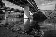 Una pareja de jovenes salen del Rio Bravo, frontera natural con los Estados Unidos mientras otro pesca bajo el puente fronterizo con los Estados Unidos. Al frente, los Estados Unidos. Matamoros, Tamaulipas. Fotografo César Rodríguez.