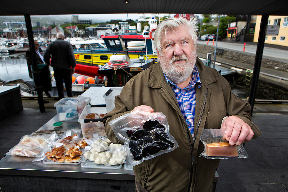 """Mårten Johannesen, a 71 year old retired boat captain supplements his finances by selling fish and pilot whale meat in Torshavn harbor on the island of Streymoy.  Marten says half his customers are tourists-curious to try the dried whale meat.  Johannesen himself eats the whale meat once a week.  He believes that the islanders will continue hunting-a process that is now """"fully controlled, and compassionate towards the animals.""""<br /> <br /> Johannessen holds up samples of dried pilot whale meat (left) and pilot whale blubber (right).<br /> <br /> Torshavn Harbor, Streymoy Island, Faroe Islands."""