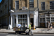 Street cleaner pulling a rubbish collection cart in Argyle Street, Bath, Somerset, England