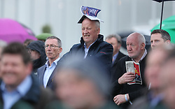 A punter uses a race card to keep his head dry during day one of the Punchestown Festival at Punchestown Racecourse, County Kildare, Ireland.