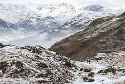 © Licensed to London News Pictures. 20/01/2019. Lake District, UK. People walk to the summit of Loughrigg Fell in the Lake District as the surrounding mountains are covered in snow and fog fills the valleys during cold weather. Photo credit : Tom Nicholson/LNP