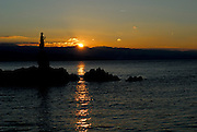 Statue of Lady with Seagull at sunrise, with reflection of rising sun in water. Opatija, Croatia