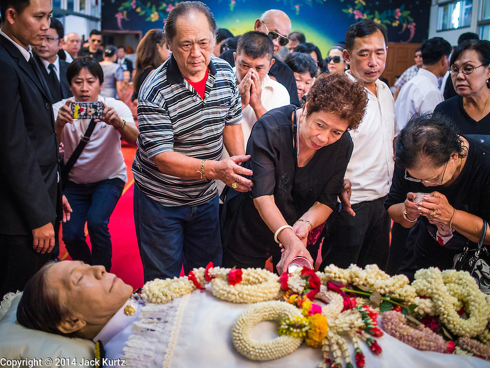 12 OCTOBER 2104 - BANG BUA THONG, NONTHABURI, THAILAND: People pay respects to Apiwan Wiriyachai, whose funeral rites started at Wat Bang Phai in Bang Bua Thong, a Bangkok suburb, Sunday. Apiwan was a prominent Red Shirt leader, member of the Pheu Thai Party of former Prime Minister Yingluck Shinawatra, and a member of the Thai parliament. The military government that deposed the elected government in May, 2014, charged Apiwan with Lese Majeste for allegedly insulting the Thai Monarchy. Rather than face the charges, Apiwan fled Thailand to the Philippines. He died of a lung infection in the Philippines on Oct. 6. The military government gave his family permission to bring him back to Thailand for the funeral. He will be cremated later in October. The first day of the funeral rites Sunday drew tens of thousands of Red Shirts and their supporters, in the first Red Shirt gathering since the coup.    PHOTO BY JACK KURTZ
