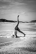 Florianopolis, Brazil - April 9, 2019: Lais, from Brazil, performs a headstand on a sunny afternoon on a stretch of pristine sand between Campeche and Joaquina beaches in Florianopolis, Brazil.