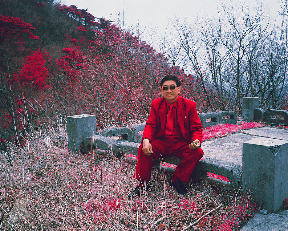 A suit-wearing man takes a break on the road between Pyongyang and Wonsan. North Koreans dress conservatively most of the time and, in this highly militarized nation, army uniforms are common sight.