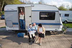 Family sitting outside their caravan in the sunshine,