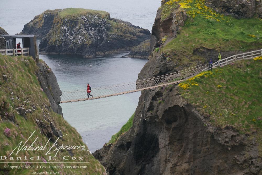 Crossing the rope bridge at Carrick-a-rede Rope Bridge National Trust, Ireland.