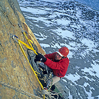 BAFFIN ISLAND, Nunavut, Canada. John Catto (MR) drags big haul bags with pulley system, en route to high camp on huge Great Sail Peak, above frozen lake in Stewart Valley.