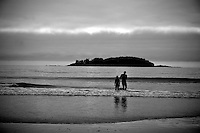Two surfers wade into the Pacific Ocean at Chesterman Beach Pacific Rim Park, Vancouver Island BC - black and white photo