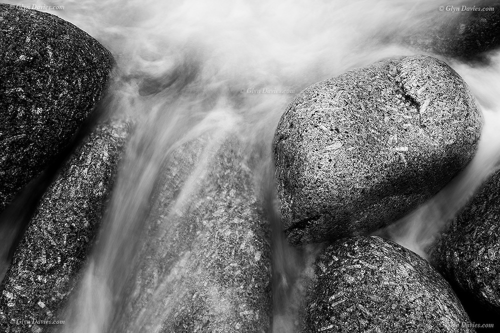 Waves on an incoming tide  flow around large granite boulders on the shoreline of the Atlantic Coast at Sennen, West Penwith Cornwall.