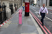 A man walks past social distance shopping tape for shoppers to queue along in Lombard Street during the Coronavirus pandemic, <br /> in the City of London, the capitals financial district, on 20th July 2020, in London, England.