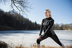 Woman with headphones doing stretching by frozen lake