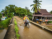 17 JUNE 2016 - DON KHONE, CHAMPASAK, LAOS: A Lao family rides their motorcycle across the bridge connecting Don Khon and Don Det islands in 4,000 Islands. Don Khon Island, one of the larger islands in the 4,000 Islands chain on the Mekong River in southern Laos. The island has become a backpacker hot spot, there are lots of guest houses and small restaurants on the north end of the island.        PHOTO BY JACK KURTZ