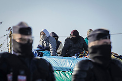 © Licensed to London News Pictures. 02/03/2016. Calais, France. Migrants attempt to resist police by camping out on the roof of a temporary building at the migrant camp knows as 'The Jungle' in Calais, France, where part of the camp is currently being cleared by French authorities. Violence has broken out in parts of the eviction zone where inhabitants have resisted efforts to move them. Photo credit: Rob Pinney/LNP
