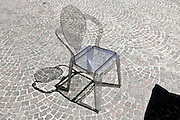 grey transparent chair with its reflection at an outdoor public cafe terrace