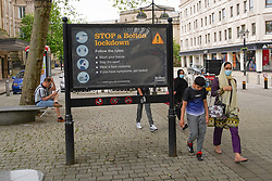 © Licensed to London News Pictures. 29/05/2021. Bolton,UK. Members of the public walk past a Covid-19 sign in Bolton town centre. Bolton has the highest Covid-19 infection rate in the country as the Indian variant of Covid-19 continues to spread.  Photo credit: Ioannis Alexopoulos/LNP