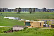 Nederland, Brummen, 10-5-2019 Het landschap tussen Voorst en Cortenoever, vlakbij Zutphen, is een gebied dat door de IJssel is gevormd. Met uitgestrekte uiterwaarden, stroomruggen en een aantal scherpe rivierbochten. Om het gebied langs de IJssel te beschermen tegen hoogwater zijn op twee plekken dijken landinwaarts verlegd. Zo is er meer ruimte voor de rivier wanneer het nodig is. Bij het verhogen van de waterveiligheid is op een slimme manier gebruik gemaakt van bestaande dijken in het gebied. Die zijn op strategische locaties – in het noorden en zuiden – verlaagd. Bovendien hebben de drempels verschillende hoogten. Daardoor stromen de uiterwaarden bij hoogwater gecontroleerd mee met de rivier en blijft de stroomsnelheid beperkt. Zo treedt er minder schade op. Als de waterstand in de IJssel weer zakt, zakt ook de waterstand in de overstroombare gebieden. Nieuw aangelegde gemalen pompen dan het laatste water uit het gebied, waardoor het snel weer droog is. Foto: ANP/ Hollandse Hoogte/ Flip Franssen