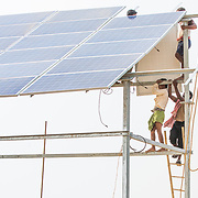 CAPTION: Installing the final module on the first solar panel at the OORJAgram Rural Enterprise Zone. LOCATION: Diara Rasulpur, Saran District, Bihar, India. INDIVIDUAL(S) PHOTOGRAPHED: N/A.