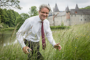Interior architectThierry THENAERS smiles after having taken a photograph of the Castle of Anthée with pond, in Anthée, Belgium, 10th of June 2013. Credit Sander de Wilde for The Wall Street Journal.  Castle
