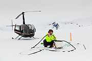 U. S. Geological Survey glaciologist drills a hole into the snow layer with a steam drill to install a mass balance wire on the surface of Columbia Glacier, Alaska.