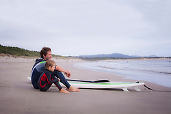 Father with son looking at view and sitting on beach, Viana do Castelo, Norte Region, Portugal