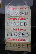 The repetition of a sign hanging in a shop's window in south London. We see a detail of the notice on the outside of a local business called carpet Corner which is apparently closed today and its trading statement is repeated four times.