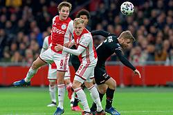 Carel Eiting #8 of Ajax, Donny van de Beek #6 of Ajax and Fredrik Midtsjo #6 of AZ Alkmaar in action during the Dutch Eredivisie match round 25 between Ajax Amsterdam and AZ Alkmaar at the Johan Cruijff Arena on March 01, 2020 in Amsterdam, Netherlands