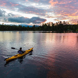 A man paddles his kayak on Long Pond in Maine's north woods. Near Greenville, Maine.