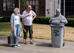 "© Licensed to London News Pictures; 15/06/2020; Bristol, UK. People view and photograph a new mystery statue of a caricature Englishman has been placed by the now empty Colston plinth on Monday morning, following an ""All Lives Matter"" protest at the weekend to ""defend the Cenotaph"". The grey statue shows a bald man resting in a wheelie bin with the words ""Spoiler: St George was Turkish"" on the front. He is holding a small globe in one hand and a mobile phone in the other hand with a screen showing the St George flag and words ""England for the English"". The character wears a string vest over a beer belly and looks over to where Colston's statue was torn down from its plinth a week ago. The artist is not known but the statue looks similar to ""Ruth"", a character who appeared on Victoria Street in April 2018. This comes just over a week after the statue of Edward Colston which has stood in Bristol city centre for over 100 years was pulled down by protestors and thrown in Bristol Docks during a Black Lives Matters rally and march through the city centre. The rally was held in memory of George Floyd, a black man who was killed on May 25, 2020 in Minneapolis in the US by a white police officer kneeling on his neck for nearly 9 minutes. The killing of George Floyd has seen widespread protests in the US, the UK and other countries against both modern day racism and historical legacies of slavery. Edward Colston (1636 – 1721) was a wealthy Bristol-born English merchant involved in the slave trade, a Member of Parliament and a philanthropist. He supported and endowed schools, almshouses, hospitals and churches in Bristol, London and elsewhere, and his name is commemorated in several Bristol landmarks, streets, three schools and the Colston bun. Photo credit: Simon Chapman/LNP."