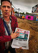 Selling the Shangri Liar, an ironic tabloit style newspaper raising money for the refugee kitchens in Calais and Dunkirk, on the Shangri La field, Glastonbury Festival 2016. The Glastonbury Festival is the largest greenfield festival in the world, and is now attended by around 175,000 people. Its a five-day music festival that takes place near Pilton, Somerset, United Kingdom. In addition to contemporary music, the festival hosts dance, comedy, theatre, circus, cabaret, and other arts. Held at Worthy Farm in Pilton, leading pop and rock artists have headlined, alongside thousands of others appearing on smaller stages and performance areas.