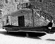 A black and white image of one of the small boats used to cross the creek in Dubai. The boat uses traditional wood working techniques and the timbers are sealed with rope in the same way as the more famous dhow. The craft is quite small, only allowing room for five or ten passengers to be shuttled across the creek.