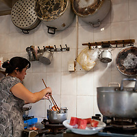 Ngân cooks in her mother-in-law's kitchen in Saigon, Vietnam.