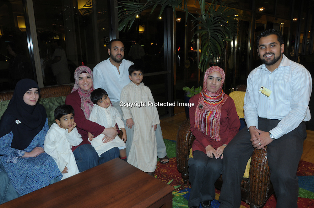 From left, Sumayya Sahin, 17, Luqman Irfan, 4, Sinan, 2, Inayet Sahin, Kashif Irfan, Murad Irfan, 7, Sobia Ijaz and Atif Irfan sit inside the lobby of the Regal Sun Resort in Lake Buena Vista, Fla., Friday, Jan. 2, 2009.  The family were not allowed to board an AirTran flight from Washington, D.C. to Orlando after passengers mistook a conversation their group had about the safest place to sit aboard their plane. (Photo by Phelan M. Ebenhack)