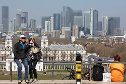 © Licensed to London News Pictures. 19/04/2021. London, UK. Members of the public take a selfie in front of the London skyline during sunny weather in Greenwich Park. Temperatures are expected to rise with highs of 17 degrees forecasted for parts of London and South East England today . Photo credit: George Cracknell Wright/LNP