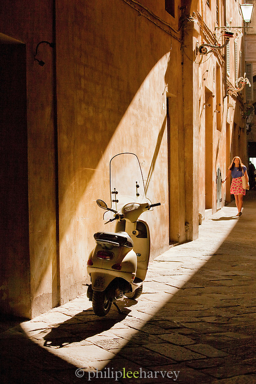 The iconic Piaggio Vespa moped, parked and illuminated by the afternoon sun in a narrow street of Siena, Tuscany, Italy