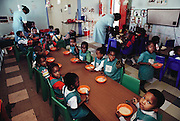 Children at the neighborhood daycare in Soweto, South Africa eat a breakfast, and a lunch, of hot pap porridge: corn meal mixed with water. This is the daycare center where Simon's son George and nephew Mateo attend while their parents are at work. The Qampie family lives in a 400 square foot concrete block duplex house in the sprawling area of Southwest Township (called Soweto), outside Johannesburg (Joberg) South Africa. Material World Project.