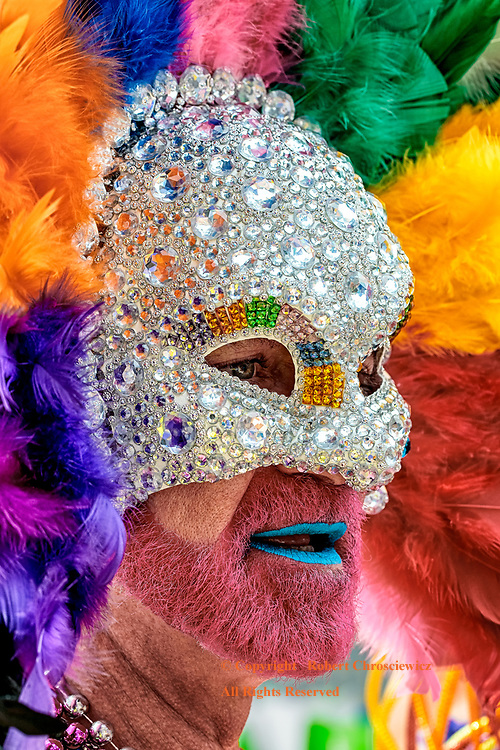 Peacock Pride: This man readies himself, behind this elaborate sequined facemask and feathered headdress, for his place in the Gay Pride Parade, Vancouver British Columbia Canada.