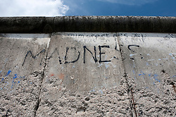 The word Madness written on original Berlin Wall at Topographie des Terrors or Topography of Terror the former Gestapo Headquarters in Berlin