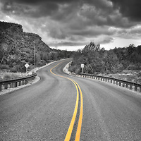 Middle of road with yellow strips heading into the end of storm clouds in Sedona, Arizona, USA.