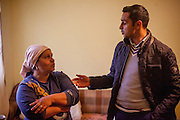 Mother Gabriela Costache (37) talking to Roma activist Marius Tudor in the living room of her family in Marginenii de Jos.