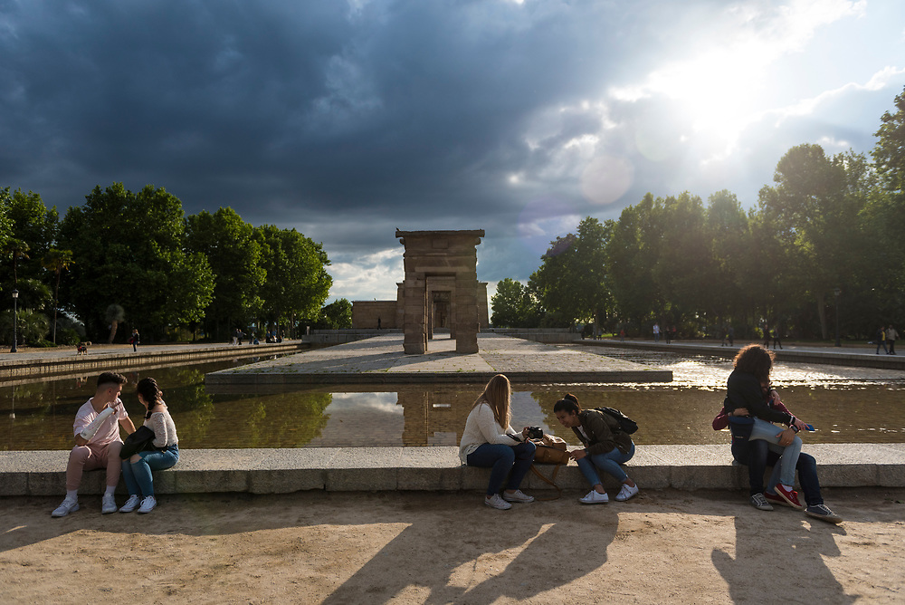 Madrid, Spain - May 25, 2018: People sit in late afternoon sunlight at the Temple Of Debod, an ancient Egyptian temple that was dismantled in Egypt during the construction of the Aswan High Dam and given as a gift from Egypt to Spain in 1968.
