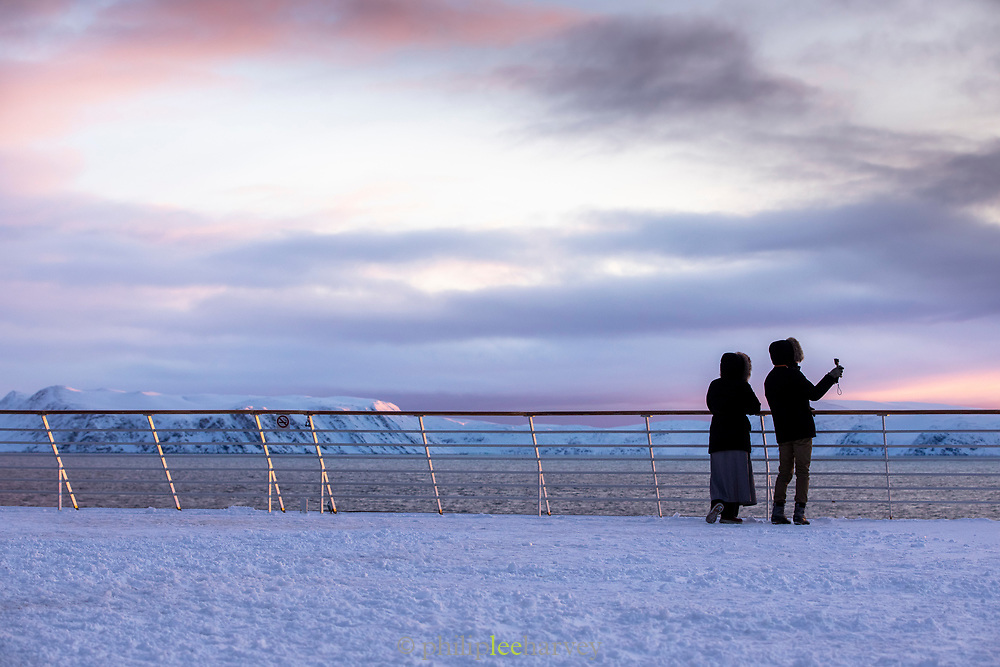 Couple looking at scenic winter landscape against dramatic sky at sunrise, Havoysund, Norway