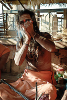 A Hindu holy man smoking a chillum at the ghats in Varanasi, Uttar Pradesh, India