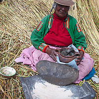 South America, Peru, Uros Islands. Uros woman grinds feed for baby chicks on the floating reed islands of Lake Titicaca.