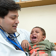 CAPTION: Gabriel was born at Hospital Escuela itself, so the doctors know his case well. He had a bilateral cleft lip and palate and has so far been operated on three times. Dr González says that after the first surgery, the results looked great on the operating table. However, within two weeks, the right side fell apart. He decided it would be prudent to wait for about four months before performing another operation. Even after the wait, the right side broke down again. After another three months, Gabriel appeared to be ready for the doctors to try once more. Alas, the surgery was unsuccessful yet again. At the time of this operation, the doctors observed that he had developed a serious cough that required him to be admitted to the Intensive Care Unit for three days. Here, it was discerned that he had anaemia and a problem in his heart that were causing the consistent breakdowns. Dr González assures that his team will ultimately succeed! He intends to operate again soon, as the situation with Gabriel's heart has improved. LOCATION: Hospital Escuela, Tegucigalpa, Honduras. INDIVIDUAL(S) PHOTOGRAPHED: Dr Luis González (left) and Luis Gabriel Erazo Artiaga (right).
