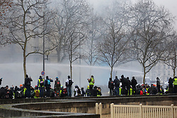 19 January 2019. Paris, France.<br /> Gilets Jaunes - Acte X take to the streets of Paris. CRS Riot police fire tear gas and shoot a water canon at a hard core of agitators intent on disrupting events at the end of the march. An estimated 7,000 people took part in the looping 14 km route from Place des Invalides to protest tax hikes from the Government of Emmanuel Macron imposed on the people. An estimated 80,000 people took part in protests across the country. Regrettably the movement has attracted a violent element of agitators who often face off with riot police at the end of the marches which tends to deflect attention away from the message of the vast majority of peaceful protesters.<br /> Photo©; Charlie Varley/varleypix.com