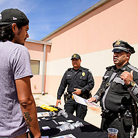 New Mexico State Police officers Christian Roman, right, and William Velasquez speak with potential recruits at a job fair hosted by New Mexico Workforce Connections, Thursday, August 30, 2018 in Gallup.