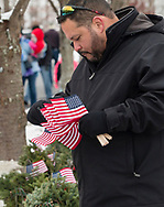 Goshen, New York - A man gets ready to place an American flag on a wreath  during a Wreaths Across America ceremony at Orange County Veterans Memorial Cemetery on Dec. 16, 2017. About 3,000 wreaths were placed at graves, and small American flags were added to the wreaths at veterans' graves.