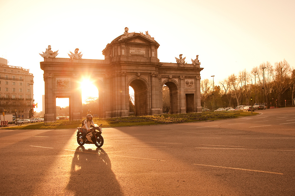 Madrid, Spain - April 05, 2010: Motorcyclist passing by in front of sunlight at Puerta de Alcala in Plaza de la Independencia.